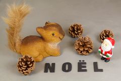 Squirrel a estatueta, a estatueta de Santa Claus, os cones do pinho e a palavra Imagens de Stock Royalty Free