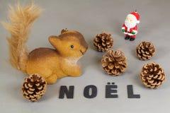 Squirrel figurine, figurine Санта Клауса, конусы сосны и слово Стоковые Изображения