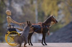 Squirrel with horse and a skeleton  on a coach Royalty Free Stock Image
