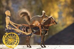 Squirrel on horse with skeleton  and coach Stock Photo
