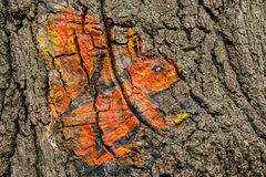 The squirrel is painted on the bark of the tree in orange in yellow colors. Royalty Free Stock Photo