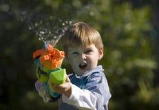 Squirt Gun Kid. Boy having fun with a squirt gun stock photos