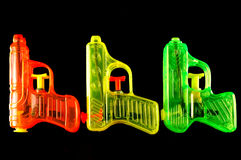Squirt Guns. Three toy squirt guns isolated on a black mirrored background stock photo
