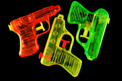 Squirt Guns. Three toy squirt guns isolated on a black mirrored background royalty free stock photos