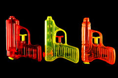Squirt Guns. Three toy squirt guns isolated on a black mirrored background stock image