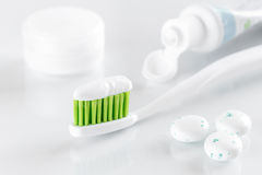 Sqweezed green toothbrush with bubble gum on white background Royalty Free Stock Photo