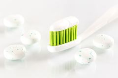 Sqweezed green toothbrush on white background with bubble gums Stock Photos