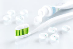 Sqweezed green toothbrush on white background with bubble gums Stock Image