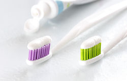 Sqweezed toothpaste and two toothbrush on white background Royalty Free Stock Image