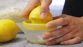 Sqweezing lemon and making juice. Woman sqweezing lemon and making juice while cooking in the kitchen stock video