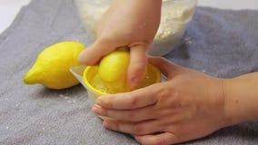 Sqweezing lemon and making juice. Woman sqweezing lemon and making juice while cooking in the kitchen stock footage