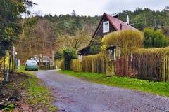 Srbska Kamenice,捷克共和国- 2017年4月08日:顶房顶在木篱芭后的村庄沿导致岩石外型的石渣道路  库存照片
