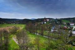 Srbska Kamenice, repubblica Ceca - 8 aprile 2017: fiume Kamenice che attraversa villaggio con una chiesa sulla collina in primave immagine stock libera da diritti