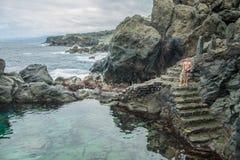 Sre отца и дочери идя поплавать в естественном бассейне Charco De Ла Laja, на севере Тенерифе Стоковое Фото