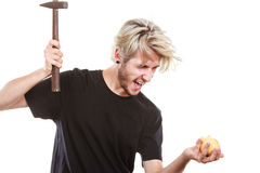 Sreaming man trying break piggy bank with hammer. Money, savings, finances concept. Angry sreaming young blonde man wearing black t shirt trying to break piggy Royalty Free Stock Photos