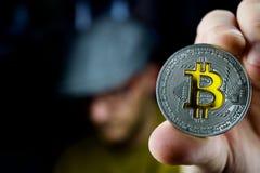Srebna bitcoin moneta w mężczyzna ręce Zdjęcia Stock