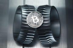 Srebna Bitcoin waluty crypto moneta kłama na gearwheel zdjęcia stock