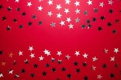 Srebna gwiazda kropi na czerwonym backgound Świąteczni wakacyjni confetti świętowania pojęcia odosobniony biel Odgórny widok, mie obrazy stock