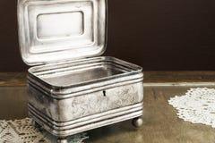 Srebna szkatuła, biżuterii, błyskotki pudełko na retro stole/ Obraz Royalty Free