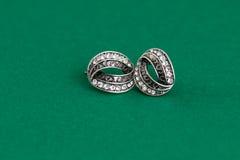 Srebni kolczyki odizolowywający na zielonym tle Zdjęcia Royalty Free
