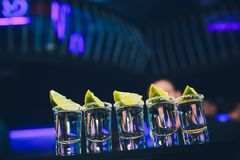 Srebni tequila strzały z lodem i wapnem na czerni zgłaszają tło obrazy stock