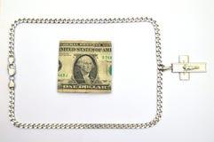 Srebny łańcuch z krucyfiksem i jeden dolarowym rachunkiem Obrazy Royalty Free