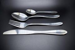 Srebny cutlery ustawiający przeciw ciemnemu tłu z miękkim cieniem zdjęcie stock
