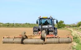 Srebny Jcb fastrac pracuje w polu z rolownikiem Obrazy Royalty Free