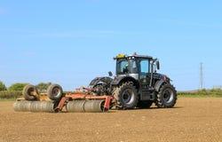 Srebny Jcb fastrac pracuje w polu z rolownikiem Zdjęcia Stock