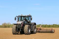 Srebny Jcb fastrac pracuje w polu z rolownikiem Zdjęcia Royalty Free