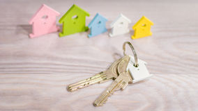 Srebny Keychain kłaść na drewnianej powierzchni przed miniaturowym symbolem różnorodni coloured domy zostaje w linii obrazy stock