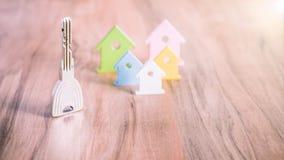 Srebny Kluczowy zostawać na drewnianej powierzchni miniaturowy symbol różnorodni coloured domy behind obraz royalty free