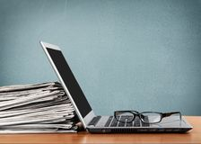 Srebny laptop z szkłami i rozsypiskiem papiery Fotografia Stock