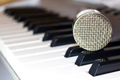 Srebny mikrofon na klawiaturowym syntetyku fotografia stock