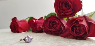 srebny projektanta pierścionek z dużym fiołkowym klejnotu kamieniem blisko czerwonych róż fotografia stock