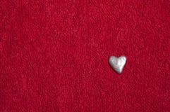Srebny serce na czerwonej tkaninie fotografia stock