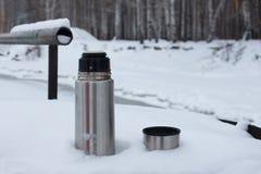 Srebny termos z kawą lub herbatą jest w śniegu w tło śnieżystym brzeg rzekim obrazy royalty free