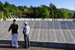 Srebrenica Genocide Memorial. A Bosnian Muslim men, a survivor of the Srebrenica massacre, read the names of Muslims killed in Srebrenica Stock Photos