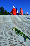 Srebrenica - Potocari, Bosnia and Herzegovina. A Bosnian Muslim women, read the names of Muslims killed in the former UN safe zone of Srebrenica Royalty Free Stock Photo