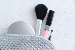 Srebrzysta kosmetyczna torba z prochowym muśnięciem dla prochowej wargi glosy i makeup szczotkujemy zdjęcie royalty free