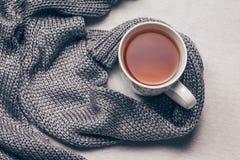 Srebrzysty siwieje trykotową tkaninę wzdłuż filiżanki herbata na milky białym futerkowym tle Dostaje nad grypowym pojęciem Odgórn zdjęcie stock