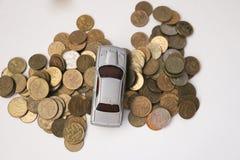 Srebrzysty zabawkarski samochód na srebrzystych i złotych monetach odizolowywać na białych półdupkach Obraz Royalty Free