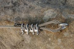 Srew with steel rope anchored into rocky wall. Difficult way on a exposed ridge in Via Ferrata twisted trip stone spiral slovenia shackle screws ring rescue royalty free stock photo