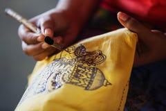Sri Lanka. Create traditional art - batik. Spouted tool - cantin. Sri Lanka, Anuradhapura. Artist sketching with an instrument to create a traditional work of Stock Photos