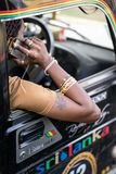 Fancy man talking on cellphone. Sri Lanka - 02 February 2018: man rastafarian with tattoo on his arm is talking on cellphone in the black car with colorful stock images