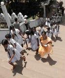 Sri Lanka school class visiting Matale temple. School class in white uniform on bare feet visiting Matale temple Sri lanka with their teacher in sari Royalty Free Stock Photos