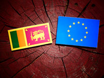 Sri Lankan flag with EU flag on a tree stump isolated. Sri Lankan flag with EU flag on a tree stump Stock Images