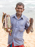 Sri Lankan man sells jewelery to tourists on the white sand beach Royalty Free Stock Photography