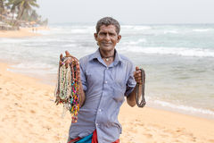 Sri Lankan man sells jewelery to tourists on the white sand beach Royalty Free Stock Images