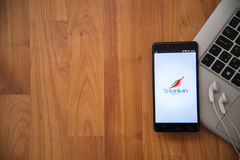 Srilankan airlines. Los Angeles, USA, april 16, 2017: Srilankan airlines application on smartphone with earphones and notebook on wooden background stock photography